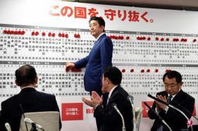 日本首相安倍在东京自民党总部的当选议员榜上钉上小红花。(法新社)