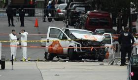 被用来行凶的小型卡车撞得毁坏不堪,事发隔天,调查人员还在现场搜证。(法新社)