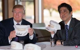 """日本首相安倍晋三(右)同到访的美国总统特朗普共进午餐后,一起打高尔夫。两人还在一些印有""""特朗普和安倍让美日同盟更加伟大""""字样的帽子上签名留念。(法新社)"""